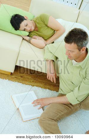 Junges Paar zu Hause ausruhen. Mann, Lektüre Stock, Frau auf Couch schlafen.