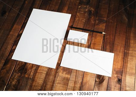 Photo of blank stationery set on vintage wooden table background. Blank ID template. Mock-up for branding identity. Letterhead business cards envelope and pencil.