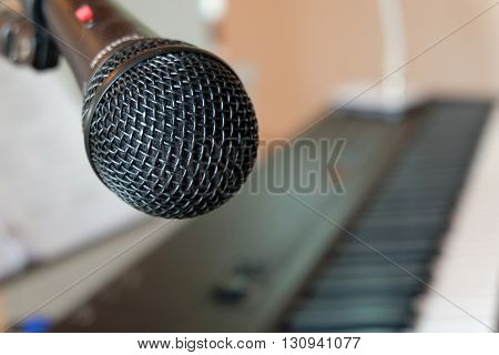 A close up microphone with a keyboard background