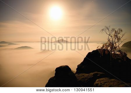 Island With Tree In Misty Ocean. Full Moon Night In  Beautiful Mountain. Sandstone Peaks  Increased