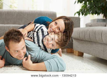 Gelukkige familie spelen thuis, volle liggend op de vloer in de woonkamer.