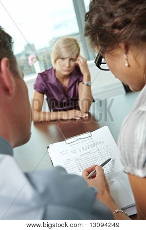 Woman applicant having failed job interview. Over the shoulder view. Focus placed on sheet in front all results are bad.