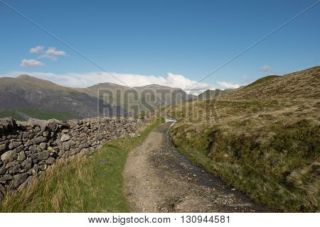 A rough track and dry stone wall runs through moorland into the distance towards mountains under a blue sky.