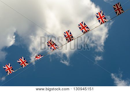 Traditional British Union Jack bunting flags of the union jack set against a bue sky and white cloud background.Nobody in the scene. copy space area.