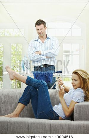 Relaxed young woman sitting on couch filing her nails, man watching with hands crossed behind ironing board. Focus on man.