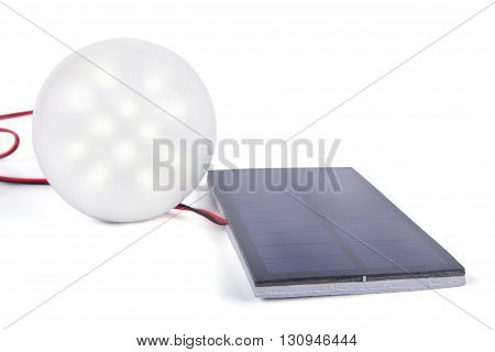 A small solar panel giving power to the LED lamp