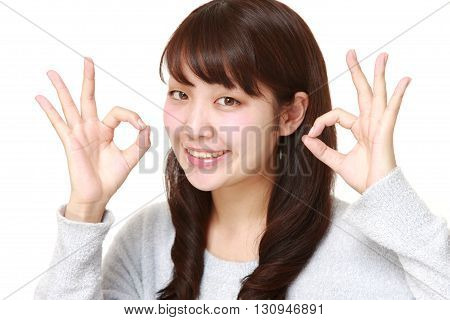 portrait of Japanese woman showing perfect sign on white background