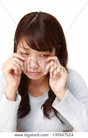 young Japanese businesswoman cries on white background