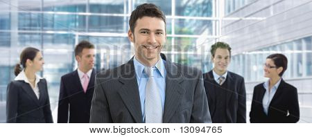 Portrait of happy businessman standing in office lounge, in front of business team, smiling.