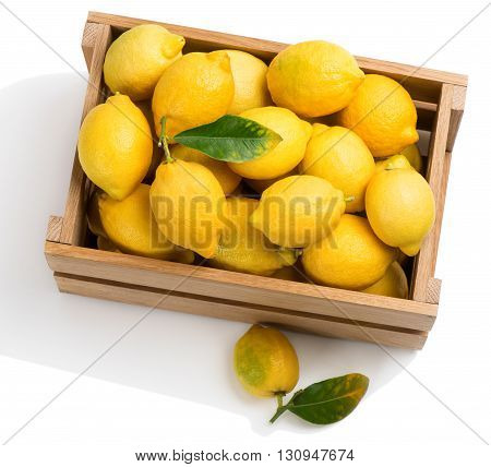 Lemons with green leaves in a wooden crate with one on the surface in the foreground isolated on white background.