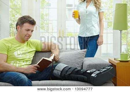 Man rasting his broken leg in cast on sofa at home, reading book.