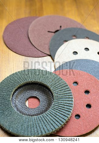 Abrasive disks for metal and stonewood grinding cutting. Set of abrasive materials on wooden background vertical view.