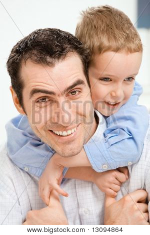 Closeup portrait of happy father holding his son on his back, smiling.