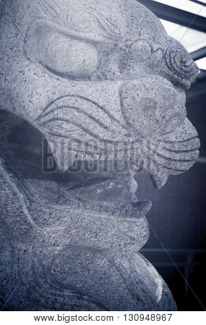 Granite sculpture of traditional chinese lion face close up selective focus