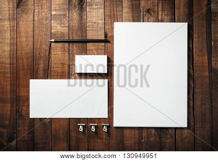 Blank stationery set on wood table background. Corporate identity template. Letterhead business cards envelope and pencil. Mock-up for branding identity for designers. Top view.