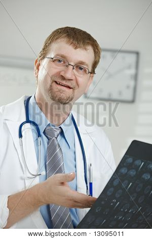 Medical office - portrait of middle-aged male doctor looking at camera explaining computer tomograph scan.