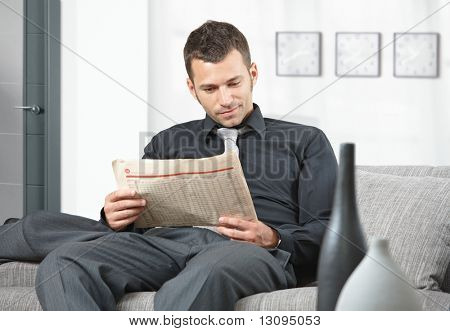 Young businessman sitting on sofa at office anteroom reading newspaper waiting.