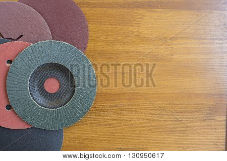 Abrasive disks for metal and stone,wood grinding, cutting. Set of abrasive materials on wooden background vertical view.