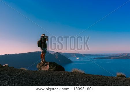 Photographer traveler takes picture caldera and Santorini island in Aegean sea, Greece