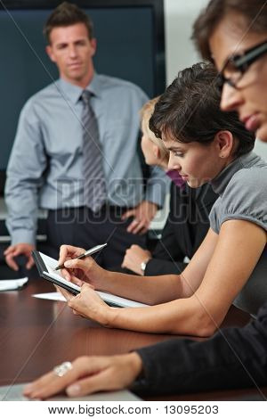 Business people sitting in a row on business training, Focus on woman in middle writing notes.
