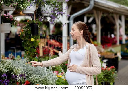 sale, shopping, pregnancy, gardening and people concept - happy pregnant woman choosing flowers at street market