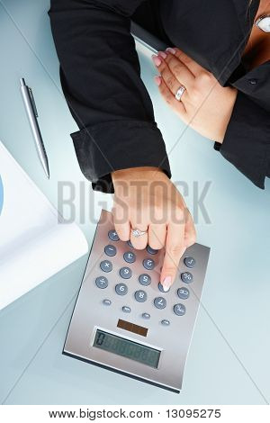 Closeup of female hands using digital calculator.