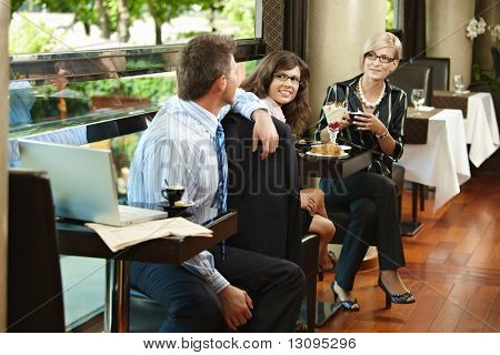 Young women having sweets in cafe, talking with businessman sitting at next table, smiling.