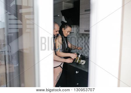 man and woman together making tea in the kitchen