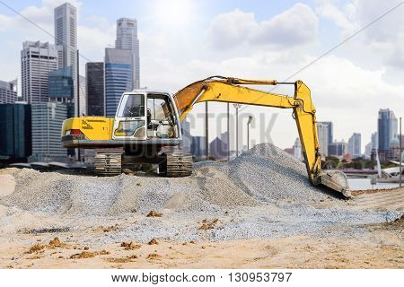 Excavator parked on the mound in the city with skyscraper background.