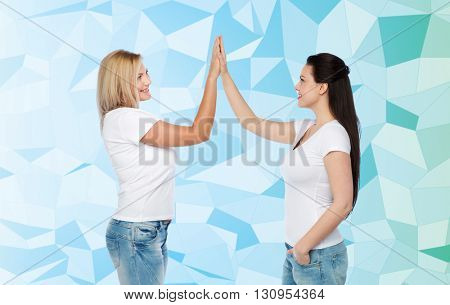 friendship, diverse, body positive, gesture and people concept - group of happy different women in white t-shirts making high five over blue low poly background