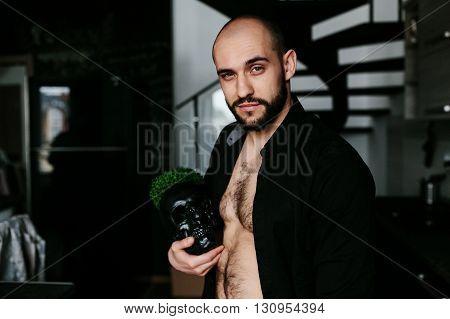 handsome, bearded man holding a black skull