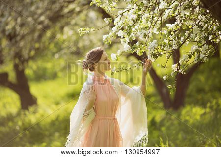 Happy young woman near the blossoming apple tree