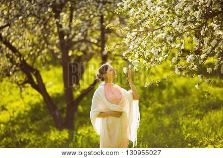 Happy beautiful young woman smelling a flower apple