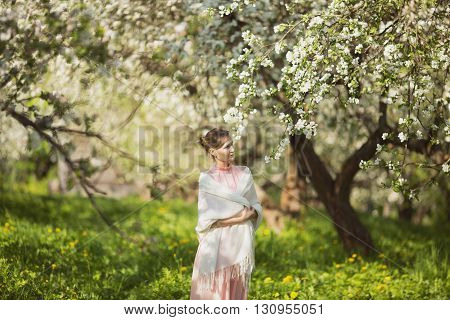 Happy beautiful young woman among apple blossom