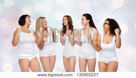 success, friendship, beauty, body positive and people concept - group of happy different women in white underwear celebrating victory over holidays lights background