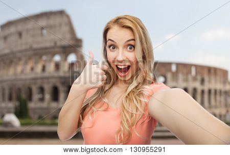 travel, tourism, emotions, expressions and people concept - happy smiling young woman taking selfie and showing thumbs up over coliseum background