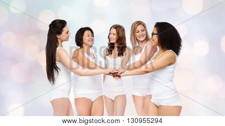 gesture, friendship, beauty, body positive and people concept - group of happy different women in white underwear holding hands together on top over holidays lights background
