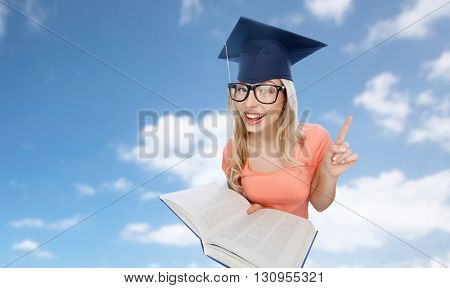 people, education, knowledge and graduation concept - smiling young student woman in mortarboard and eyeglasses with encyclopedia book pointing finger up over blue sky and clouds background