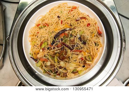 Stir fried spicy spaghetti with bacon on buffet