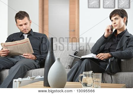 Business people sitting on sofa at office anteroom waiting.