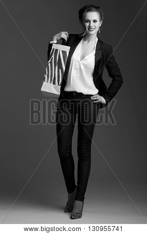 Happy Elegant Woman With Shopping Bag Against Grey Background