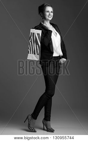Woman With Shopping Bag Looking Aside Against Grey Background
