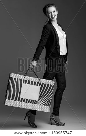 Happy Woman With Shopping Bag Posing Against Grey Background