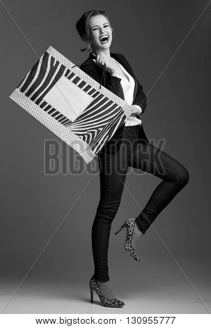 Cheerful Woman Showing Big Shopping Bag Against Grey Background