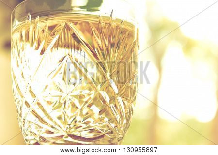 Crystal Glass with White Wine Close-up in Vintage Style