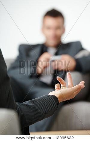 Business meeting at office. People sitting on sofa, talking. Focus on explaining female hand.