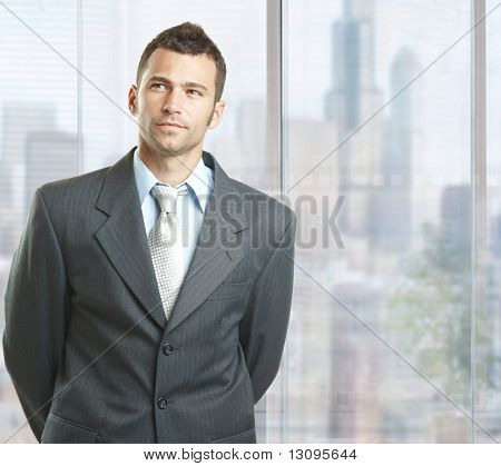Determined businessman standing in front of windows in downtown office.
