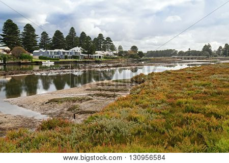 PORT FAIRY, AUSTRALIA - APRIL, 2016 : Beautiful modern houses along the Moyne River at Port Fairy in Victoria, Australia on April 13, 2016 with colorful ground cover plants in the foreground