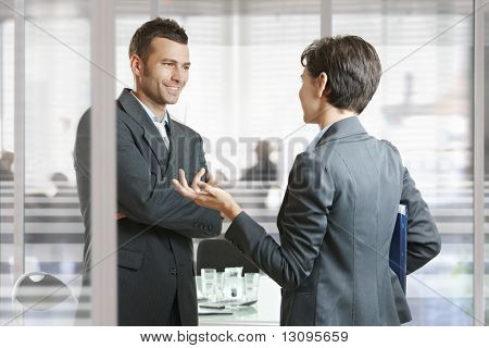 Businessman and businesswoman leaving meeting room, talking at the door, smiling.