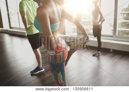 fitness, sport, training, gym and lifestyle concept - close up of people with trainer exercising and stretching leg in gym